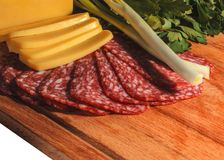 Composition of appetizing sausage, cheese, greens and onions on a wooden board, isolate stock photography