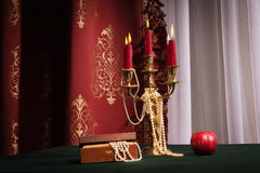 Composition with apple, candlestick and jewellery box Royalty Free Stock Images