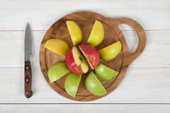 Composition of apple pieces on wooden cutting board and a knife next to it in top view. Stock Photos