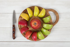 Composition of apple pieces on wooden cutting board and a knife next to it in top view. Stock Photography