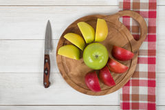 Composition of apple pieces on wooden cutting board and a knife next to it in top view. Royalty Free Stock Image