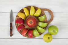 Composition of apple pieces on wooden cutting board and a knife next to it in top view. Stock Image