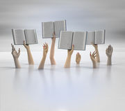 Composition of arms holding books, blur background Royalty Free Stock Images