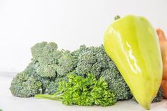Composition with assorted raw organic vegetables on white background. Yellow pepper stands on heap of broccoli sprouts, fresh parsley sprig Royalty Free Stock Images