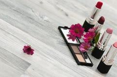 Composition avec des cosmétiques femelles sur un fond blanc, avec des fleurs roses et un endroit pour l'inscription Photographie stock