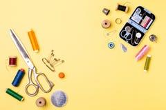 Composition avec des fils et des accessoires de couture - ciseaux, centimètre, goupilles sur le fond jaune photos libres de droits