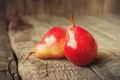 Composition avec deux poires rouges sur la table en bois Photo stock