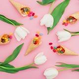 Composition avec la sucrerie de sucre lumineuse en cônes de gaufre et fleurs blanches sur le fond rose Configuration plate, vue s Image stock