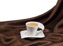 Composition avec la tasse de café au-dessus de satin brun. Image libre de droits