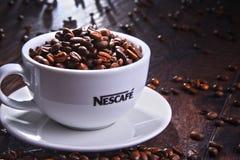 Composition avec la tasse de grains de café de Nescafe Photo libre de droits