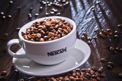 Composition avec la tasse de grains de café de Nescafe Image libre de droits
