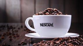 Composition avec la tasse de grains de café de Nescafe Images libres de droits