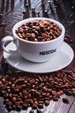 Composition avec la tasse de grains de café de Nescafe Images stock