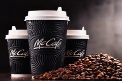 Composition avec la tasse et les haricots de café de McCafe Photos stock