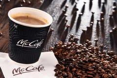 Composition avec la tasse et les haricots de café de McCafe Photo libre de droits