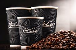 Composition avec la tasse et les haricots de café de McCafe Photographie stock libre de droits