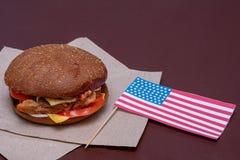 Composition avec le drapeau américain et hamburger sur le fond foncé Drapeau américain, drapeau des Etats-Unis photographie stock libre de droits