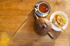 Composition avec le thé dans la tasse et la théière sur la table Photos stock