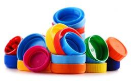 Composition avec les bouteilles et les chapeaux en plastique sur le blanc Photographie stock libre de droits