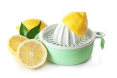 Composition avec les citrons coupés et le presse-fruits en plastique d'isolement photo stock