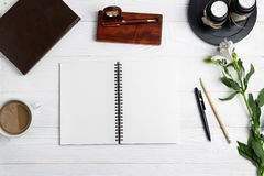 Composition avec les fleurs stationnaires de café de crayon de stylo de carnet d'éducation de bureau photo stock