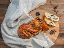 Composition avec les raisins secs, pruneaux sur un fond de vieux bois, tissu Coupez le petit pain tordu doux avec des clous de gi Photos stock