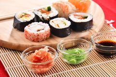 Composition avec les rouleaux de sushi et les bols assortis d'épices Photographie stock libre de droits