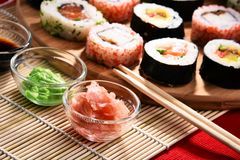 Composition avec les rouleaux de sushi et les bols assortis d'épices Image stock
