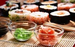 Composition avec les rouleaux de sushi et les bols assortis d'épices Photographie stock