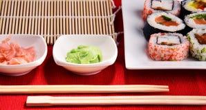 Composition avec les rouleaux de sushi et les bols assortis d'épices Photo stock