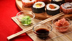Composition avec les rouleaux de sushi et les bols assortis d'épices Images stock