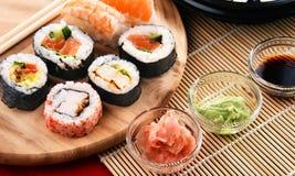 Composition avec les rouleaux de sushi et les bols assortis d'épices Image libre de droits