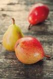 Composition avec trois poires rouges sur la table en bois Photos stock