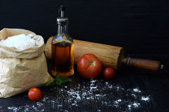 Composition of bag of wheat flour, oil, tomato and rolling pin. Preparation for kneading dough, baking pie or pizza on dark backgr. Ound. Space for text Royalty Free Stock Image