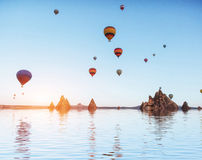 Composition of balloons over water and valleys, gorges, hills, b Stock Photos