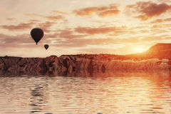 Composition of balloons over water and valleys, gorges, hills, b Royalty Free Stock Images