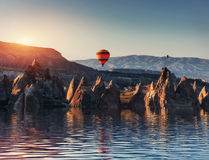 Composition of balloons over water and valleys, gorges, hills, b Stock Photo