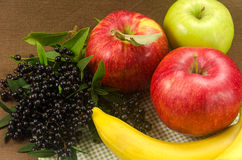 Composition with bananas, apples and dark wild berries. Raw fruits royalty free stock images