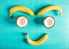 Composition of bananas and chopped halves of coconuts - a smile. On a blue background with a peel from coconut Royalty Free Stock Photos