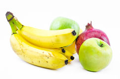 Composition of bananas, green apples and a pomegranate on a white background Stock Photos