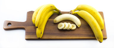 Composition of bananas one of them is peeled and cut on a wooden board and white background Stock Photography