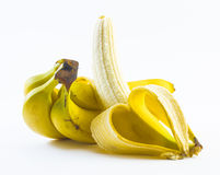 Composition of bananas one of them is peeled on a white background Stock Photos