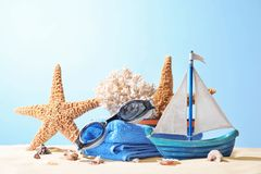Composition with beach accessories on sand against color background. stock photo