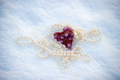 Composition of beads. And heart in the snow background Royalty Free Stock Images