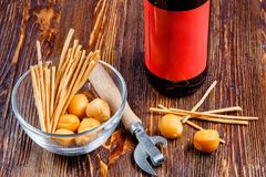 Composition of a beer on a rustic wooden table next to a bowl of salty snacks and a bottle opener. Stock Photography