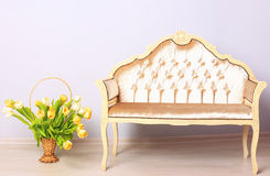 Composition in beige tones: a bench and a basket of flowers Royalty Free Stock Image