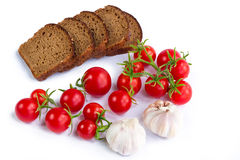 Composition of black bread slices, bunch of tomatoes and garlic Royalty Free Stock Photos
