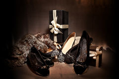 Composition black classy shoes. With spikes, ribons, shiny and gift boxes, silk background Royalty Free Stock Images