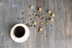 Composition of black hot coffee in a white cup, brown sugar, coffee beans and cardamon seeds Stock Images