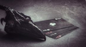 COMPOSITION OF BLACK POKER PLAYING CARDS WITH RAVEN BEAK stock photography